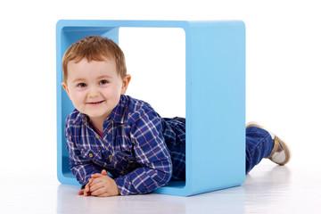 petit garçon dans un cube bleu