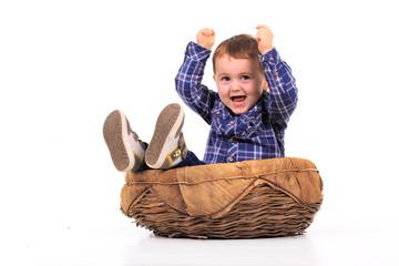 petit garçon assis dans un panier lève les bras
