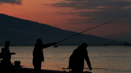 silhouette fisherman throws fishing tackles at beautiful sunset