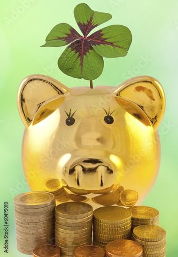 tirelire dorée, argent et trèfle porte-bonheur