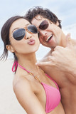 Asian Couple at Beach Taking Selfie Photograph poster