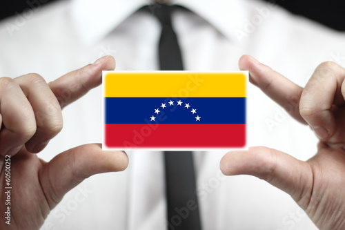 Businessman holding a business card with Venezuela Flag