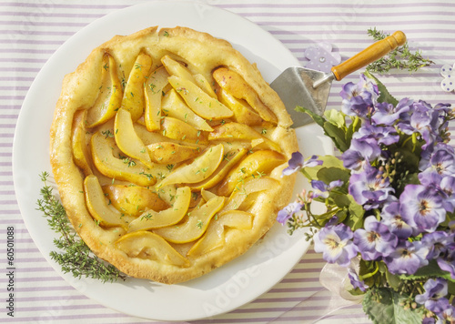 Pear tarte with thyme on purple table summerly flowers