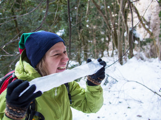 Woman eating a big icicle on a background of trees