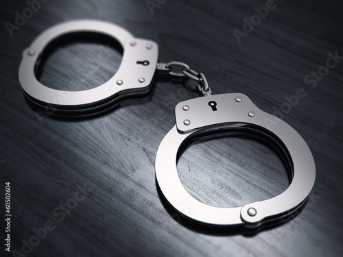 Handcuffs on wooden table