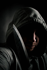 Hooded thug holding a knife