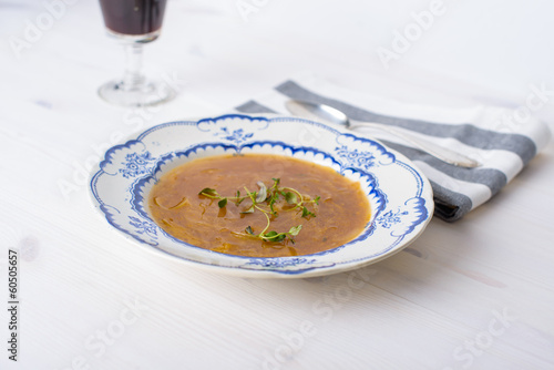 Classic french onion soup on a white wood table with some red wi