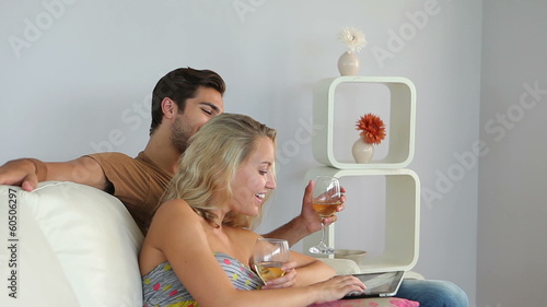 Couple lying on couch using tablet pc drinking wine