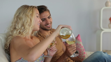 Smiling couple sitting on couch drinking wine