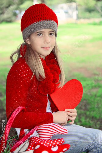 Blond girl sitting under a tree holding red felt heart