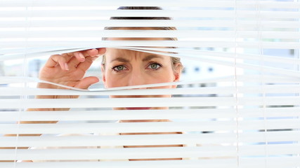 Frowning businesswoman peeking through the blinds
