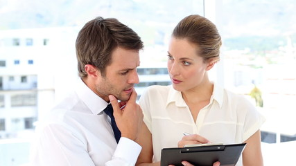Businesswoman going over checklist with colleague