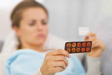 Closeup on young woman choosing pills