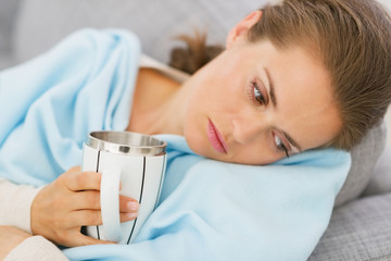 Displeased young woman with flu having cup of hot beverage