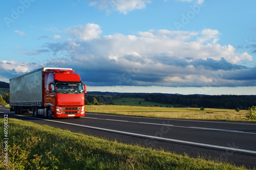 Rural landscape with road and moving red truck