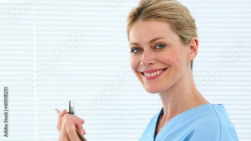 Blonde nurse holding clipboard smiling at camera