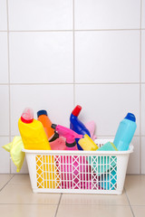 cleaning supplies in plastic basket on tiled floor