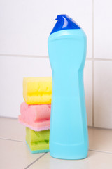 plastic bottle of cleaning product and three sponges on tiled fl
