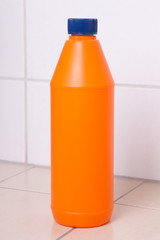 orange plastic bottle of cleaning product on tiled floor