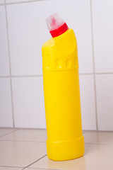 yellow plastic bottle of cleaning product on tiled floor