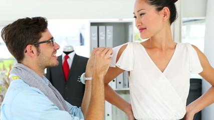 Designer adjusting sleeve of dress on model and smiling