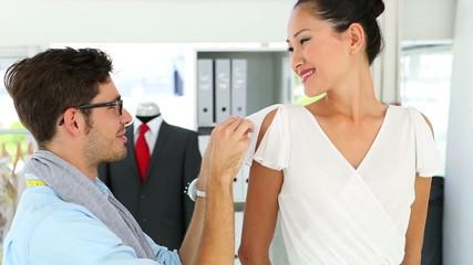 Designer adjusting sleeve of dress on model