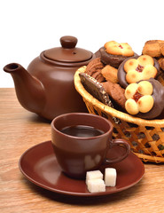 Ceramic teapot, cup and sauser with biscuits