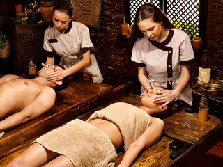 Couple having Ayurvedic spa treatment.