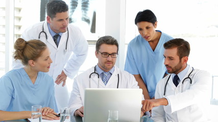 Doctor chatting with his staff during a meeting
