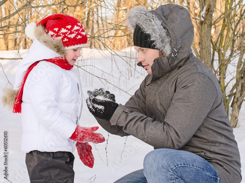 Dad shows her daughter how to make snowball.