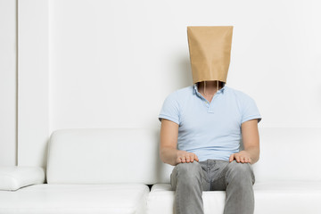 Anonymous inexpressive man with head hidden in a paper bag.