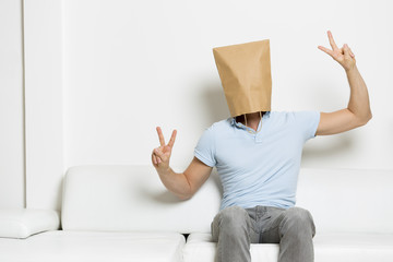 Man with head hidden in paper bag showing victory sign.