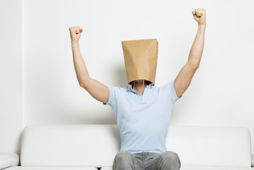 Successful anonymous man with head covered and arms in the air.