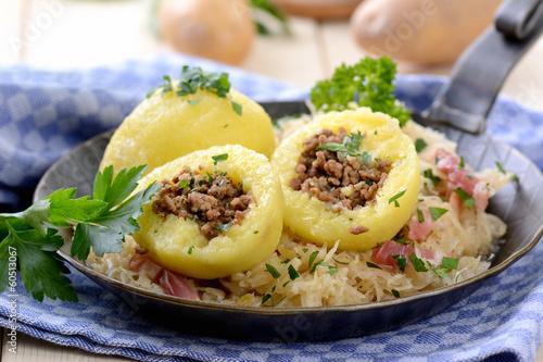 Deurstickers Klaar gerecht Gefüllte Kartoffelknödel mit Speckkraut in der Pfanne serviert