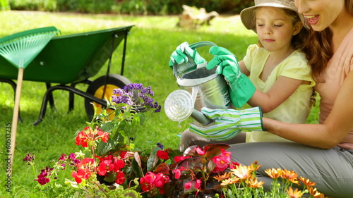 Cute girl watering the flowers with her mother
