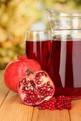 Full glass and jug of pomegranate juice and pomegranate