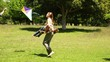 Little boy and parents flying a kite and messing in the park