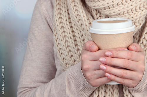 Hot drink in paper cup in hands on bright background