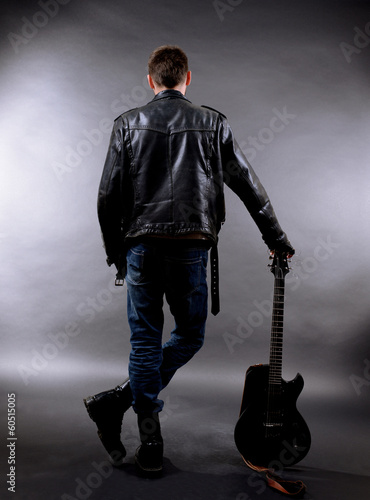 Young musician with guitar on dark color background