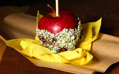 Candied apple on stick on wooden table