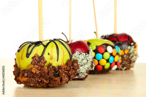 Candied apples on sticks on wooden table close up
