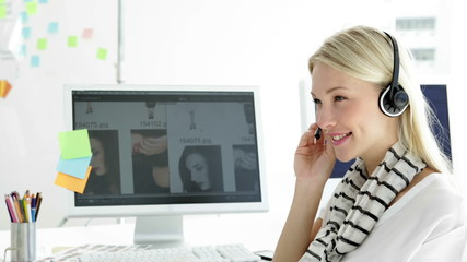 Cute blonde creative designer phoning with headset