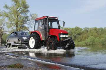 Floods, it flooded road tractor carries cars.