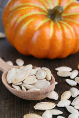 Pumpkin seeds in spoon with pumpkin on wooden background