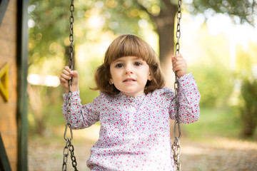 Pretty girl in park swinging