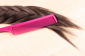 Long brown hair with comb on wooden background