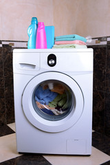 Washing machine loaded with clothes in bathroom