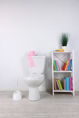 White toilet bowl and stand with books, on color wall