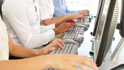Business people typing in a row