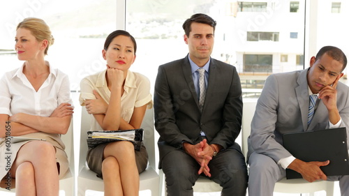Business people waiting for an interview in a row